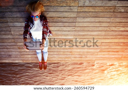 Young teen woman relaxing upon a wooden jetty while taking self portrait holding up tablet, female tourist making remembering portrait during her holidays, surrealistic photo, flare sun light, filter - stock photo