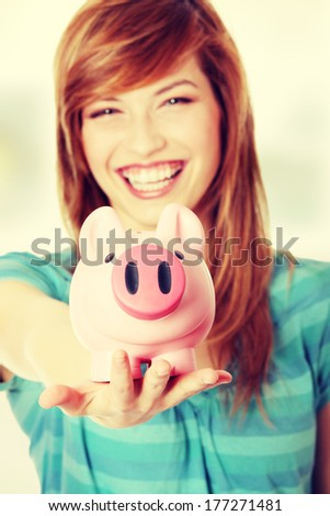 Young teen woman showing her pink piggy bank - stock photo