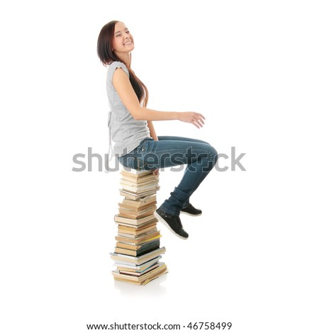 Young teen woman sitting on books isolated on white background - stock photo