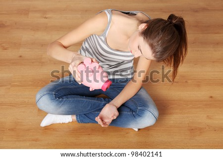 Young teen woman with her pink piggy bank - stock photo