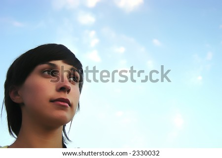 young teen woman with the blue sky as background - stock photo