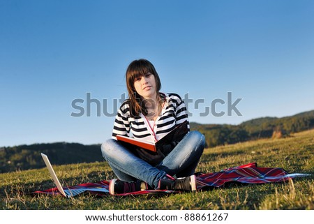young teen woman work on laptop computer outdoor in nature with blue sky and green grass in background - stock photo