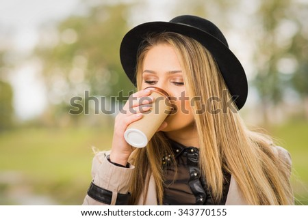 Young teenage blonde Caucasian girl in black fedora hat drinking coffee outdoors in park. Horizontal, shallow depth of field, mild retouch.  - stock photo
