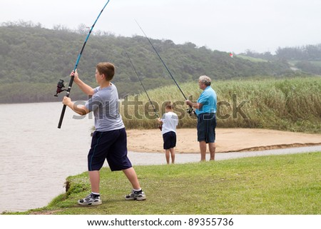 young teenage boy casting a fishing rod - stock photo