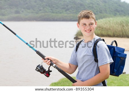 young teenage boy fishing by the lake - stock photo