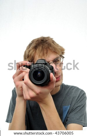 Young teenage boy holding Digital SLR Camera and pointing it at the viewer - stock photo