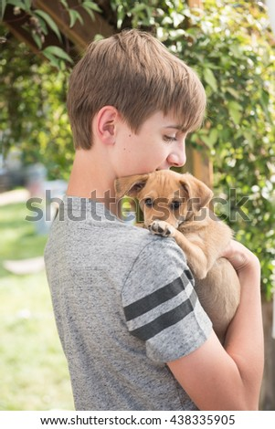 Young Teenage Boy Holding Small Terrier Mix Puppy