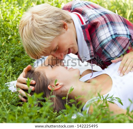 Young teenage couple in green park. - stock photo