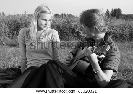 Young teenage couple in love, with the guy playing guitar