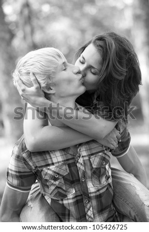 Young teenage couple in park. Photo in black and white style. - stock photo