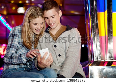 Young teenage couple sitting by a funfair ground attraction ride with colorful lights, using a smartphone during a fun night out.
