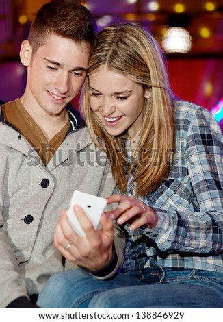 Young teenage couple sitting by a funfair ground attraction ride with colorful lights, using a smartphone during a fun night out. - stock photo