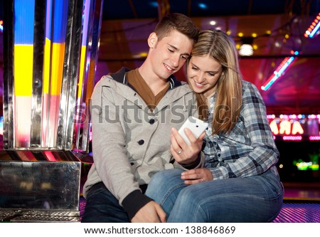 Young teenage couple sitting near a funfair attraction ride with colorful lights, using a smartphone during a fun night out. - stock photo