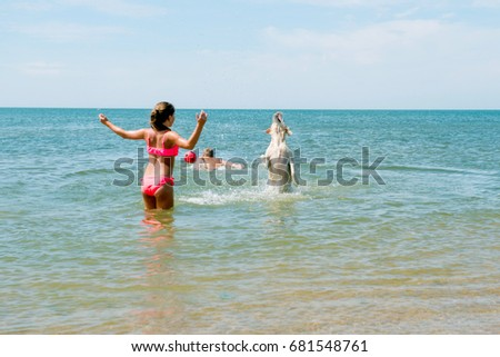 Young teenage girl and boy playing during beach vacation with dogs in the sea.