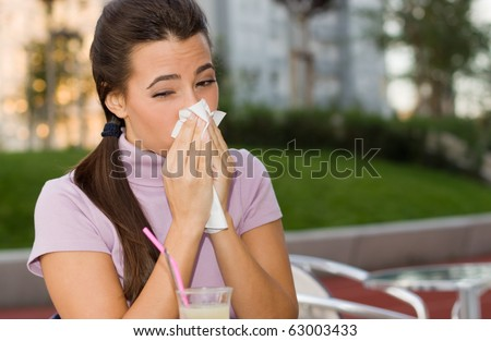 Young teenage girl blowing her nose with handkerchief. - stock photo