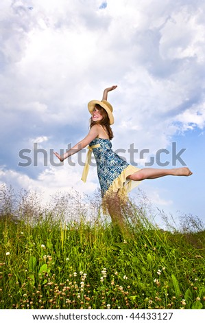 Young teenage girl dancing in summer meadow amid wildflowers - stock photo