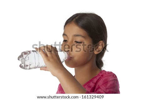 Young teenage girl drinking fresh water from a bottle on white background