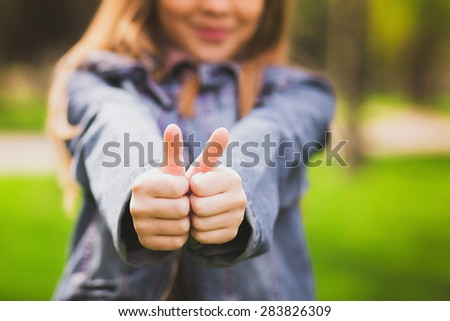 Young teenage girl giving thumb up as sign of success. Portrait of happy smiling anonymous caucasian child dressed in blue jeans casual clothing. Focus at hands. - stock photo