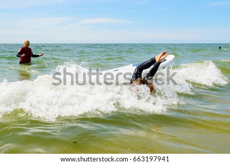 Young teenage girl having  surfing lessons.