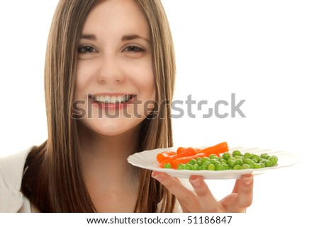 Young teenage girl holding vegetables on a plate