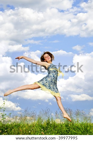 Young teenage girl jumping in summer meadow amid wildflowers