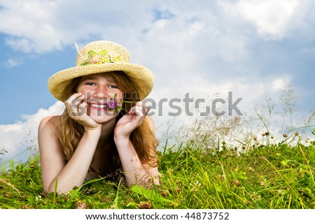 Young teenage girl laying in summer meadow resting chin on hand holding flower
