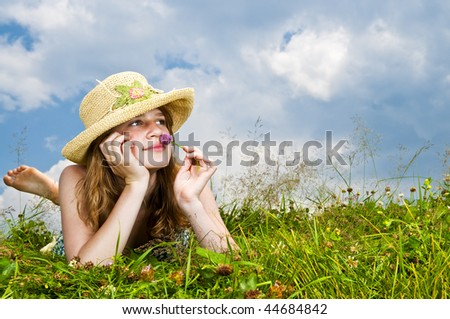 Young teenage girl laying in summer meadow resting chin on hand smelling flower