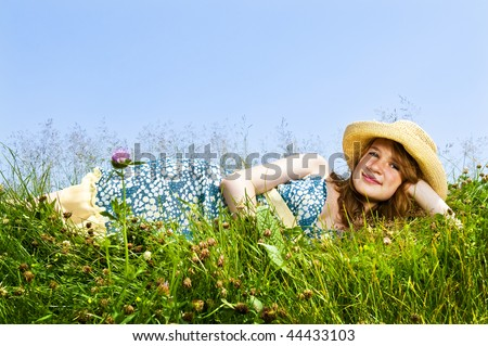 Young teenage girl laying on summer meadow in straw hat - stock photo