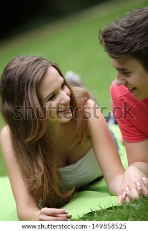 Young teenage girl on a date lying on the grass in a park holding her boyfriends hand smiling and chatting