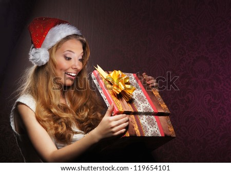 Young teenage girl opening the present - stock photo