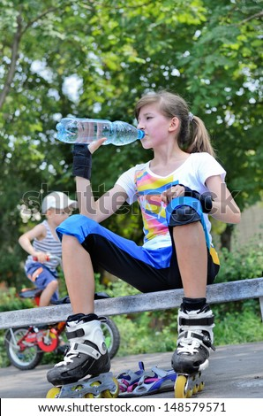 Young teenage girl pausing for a drink of bottled while roller skating sitting on a park bench with a young boy passing by on his bike behind her - stock photo