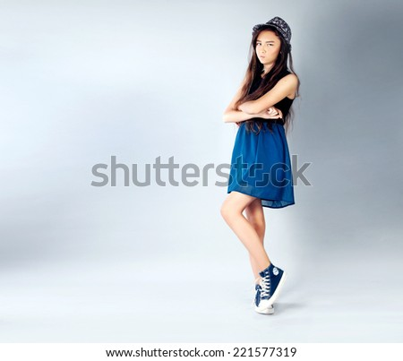 Young teenage girl posing in studio wearing fashionable clothes. - stock photo