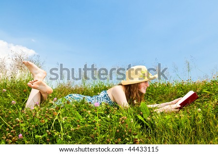 Young teenage girl reading book in summer meadow with straw hat - stock photo