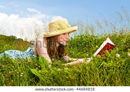 Young teenage girl reading book in summer meadow with straw hat