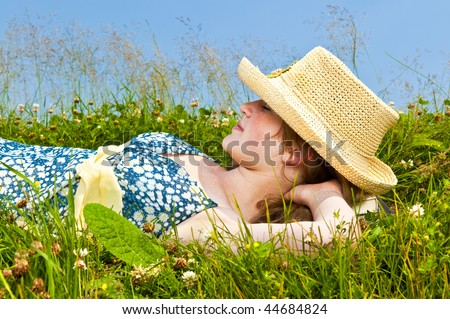 Young teenage girl resting on summer meadow in straw hat - stock photo