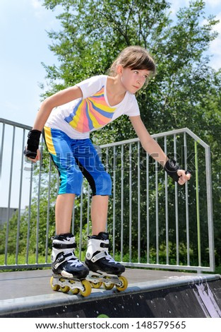 Young teenage girl roller skating balancing in her rollerblades at the top of a cement ramp in a skate park psyching herself to jump - stock photo