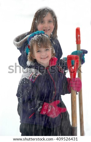 Young teenage girl shoveling snow on a winter day cold - stock photo