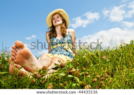 Young teenage girl sitting on summer meadow barefoot