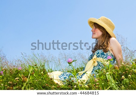 Young teenage girl sitting on summer meadow in straw hat - stock photo