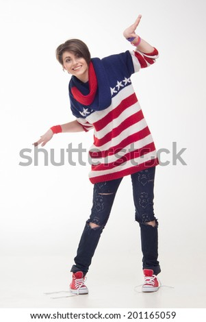 Young teenage girl smiling, waving her hands and wearing a striped pullover, torn jeans and sneakers. Concept of freedom. Isolated on the white - stock photo