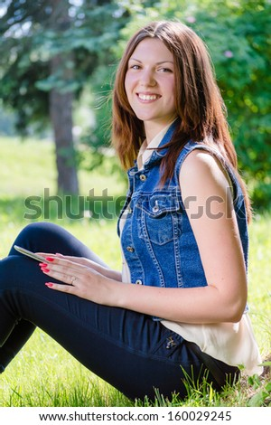 Young teenage girl student happy smiling & looking at camera sitting in park with tablet pc on summer outdoors background - stock photo