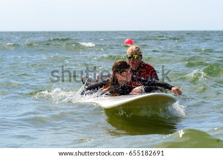 young teenage girl take surfing lessons.