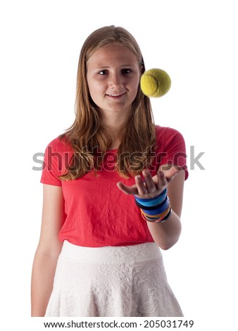 Young teenage girl throwing a tennis ball in the air over a white background - stock photo