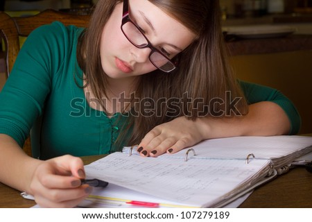 Young teenage girl with glasses doing homework - stock photo
