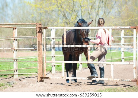 Young teenage girl with her chestnut horse in corral. Colored springtime outdoors horizontal image.