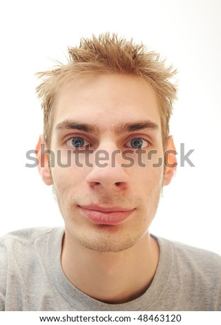 Young teenage man smirks while staring into space. Isolated on white background with room for your text.