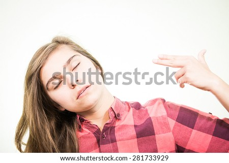 Young teenage pretending she's shooting herself in the head with her hand. - stock photo