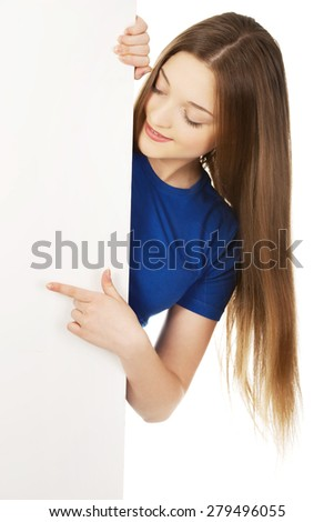 Young teenage woman pointing on blank board. - stock photo