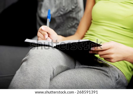Young teenage woman writing in a note. - stock photo