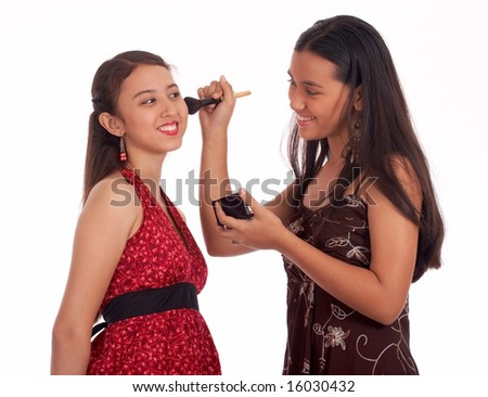young teenager applying a blush-on to her friend - stock photo